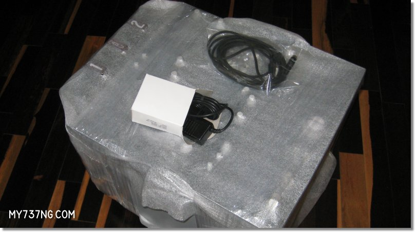 CPFlight pedestal wrapped in foam with power supply and USB cable.